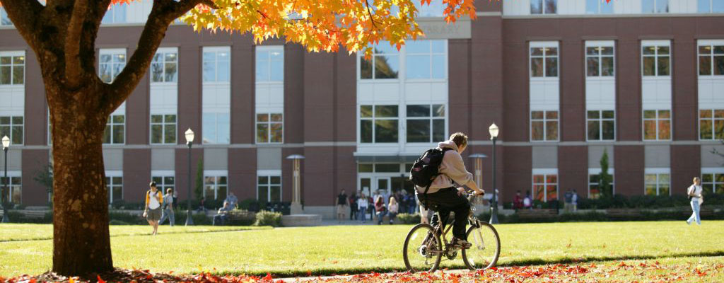 photo of student cycling through quad